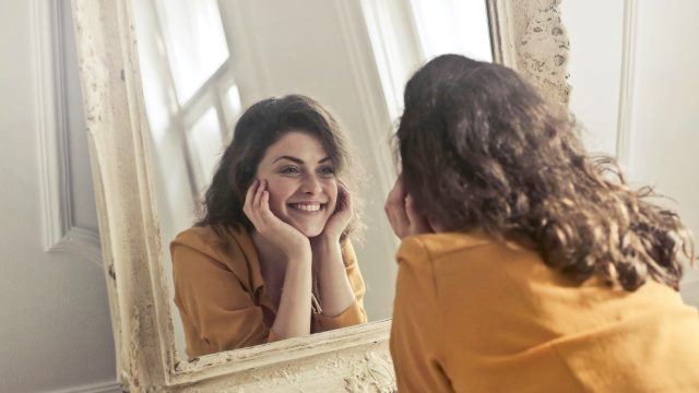 A woman look herself in the mirror and smile