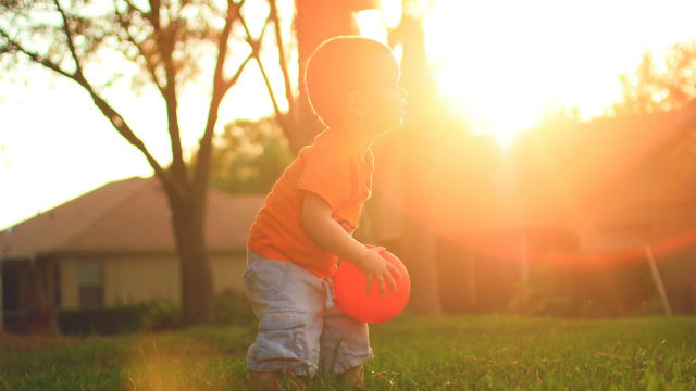 a boy playing under sunshine