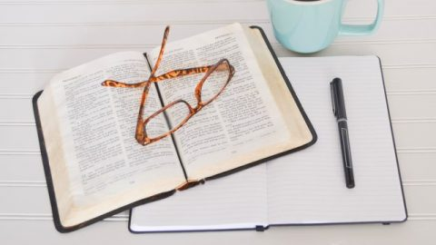 a opening bible, cup, notebook, pen