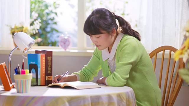 A little girl is reading the Word of God