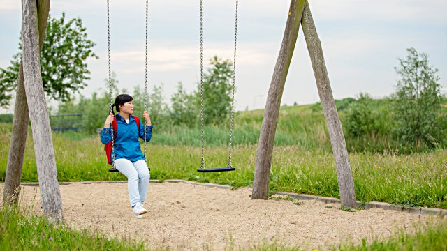 a little girl sitting on a swing