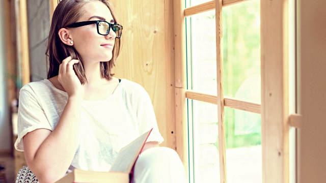 Woman wearing eyeglasses looking through window